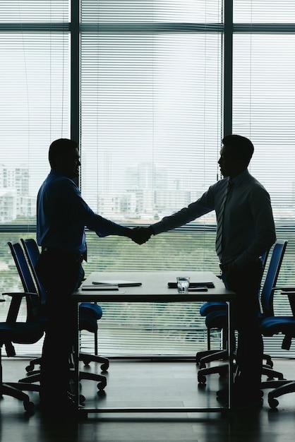 Overzichten van twee zakenmensen die handen schudden om de win-win deal te vieren Gratis Foto