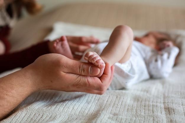 Pa houdt baby's been in zijn handen Premium Foto