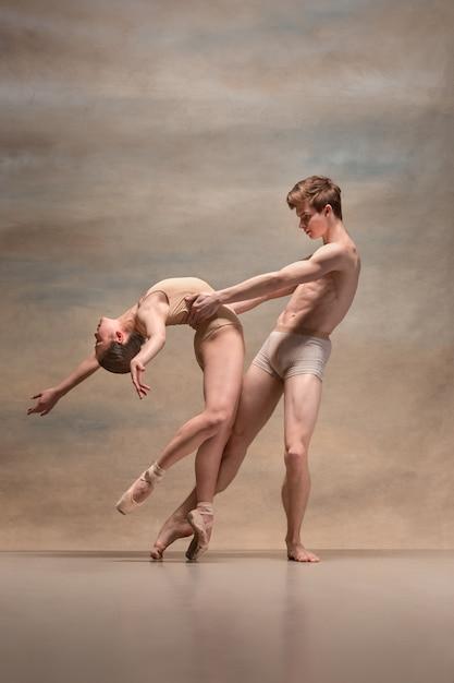 Paar balletdansers poseren over grijs. Gratis Foto