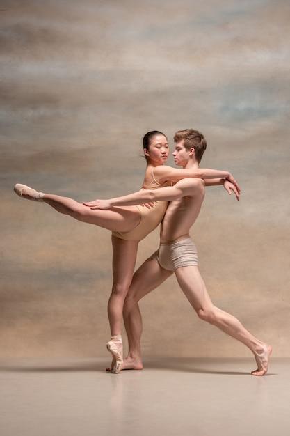 Paar balletdansers poseren over grijs Gratis Foto