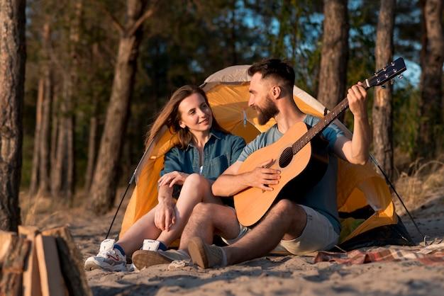 Paar bij de tent zitten en zingen Gratis Foto