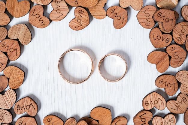 Paar bruiloft gouden ringen omlijst door houten harten op witte achtergrond. overhead schot. Premium Foto