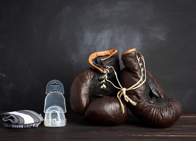 Paar bruinleren vintage bokshandschoenen, siliconen dop en polsbandage, houten achtergrond Premium Foto