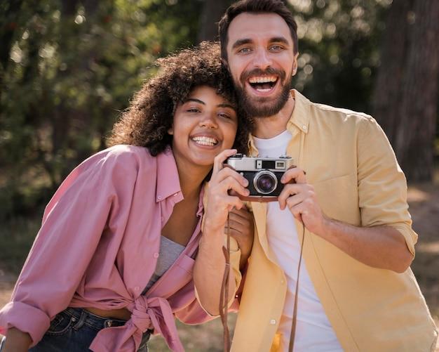Paar buitenshuis houden en fotograferen met camera Gratis Foto