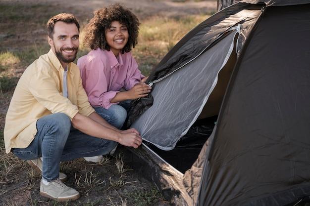 Paar buitenshuis tent samen instellen Gratis Foto