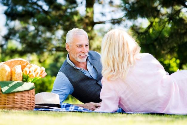 Paar dat bij een picknick in aard legt Gratis Foto