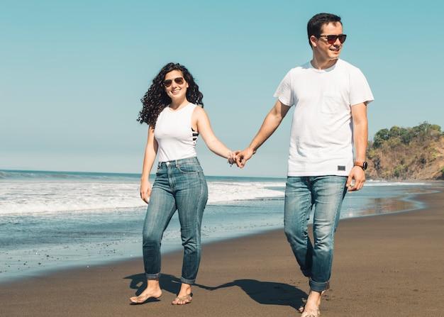Paar dat blootvoets op zandig strand loopt Gratis Foto