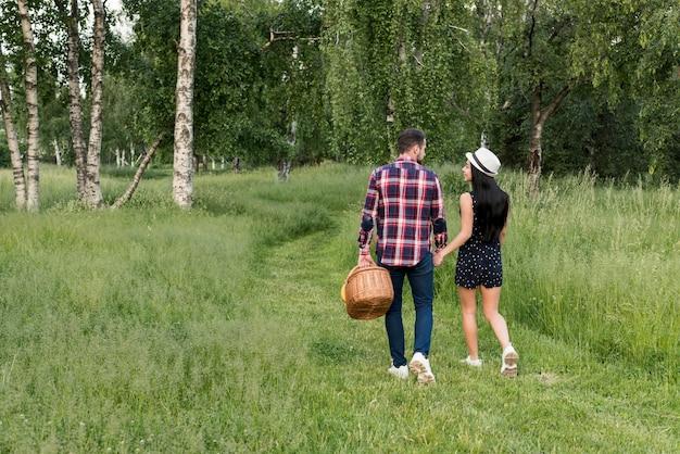 Paar dat een gang heeft die een picknickmand houdt Gratis Foto