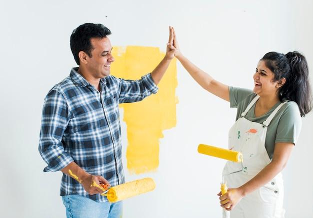 Paar dat een hoogte vijf geeft terwijl het vernieuwen van hun nieuw huis Premium Foto
