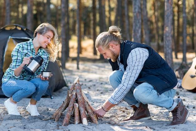 Paar dat een kampvuur in de aard maakt Gratis Foto