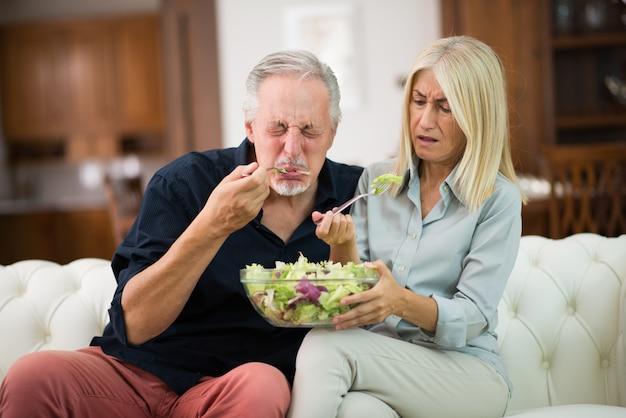 Paar dat een smaakloze salade proeft Premium Foto