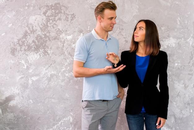 Paar dat elkaar bekijkt terwijl het houden van een reeks sleutels Gratis Foto