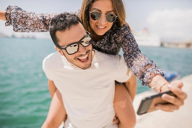 Paar dat genietend van zelfportret op celtelefoon geniet Gratis Foto