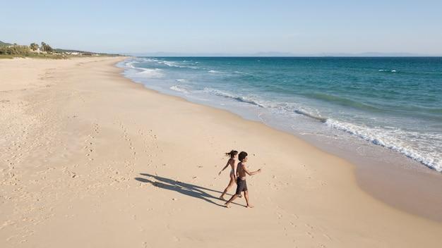 Paar dat golven langs kust gaat schuimen Gratis Foto