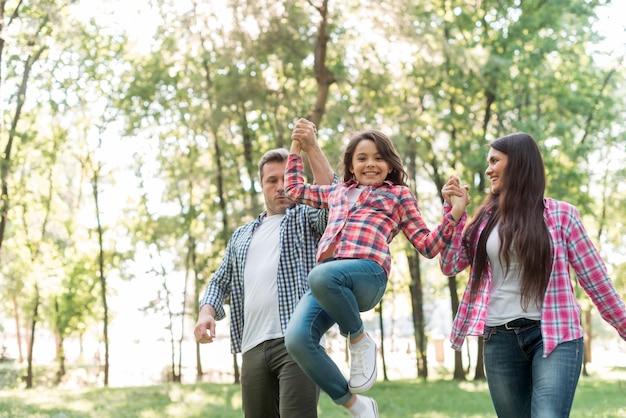 Paar dat hun dochter opheft terwijl het lopen in park Gratis Foto