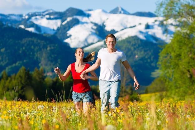 Paar dat in de weide met berg loopt Premium Foto