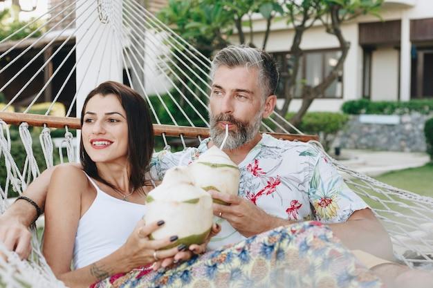 Paar dat kokosnotensap in een hangmat drinkt Premium Foto