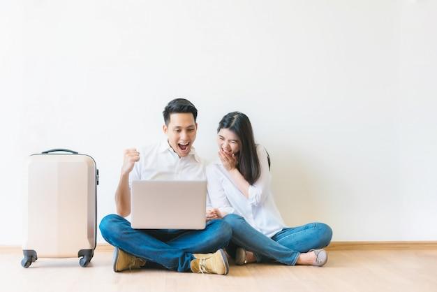 Paar dat met laptop de succesvolle reis van de planningsvakantie viert Premium Foto