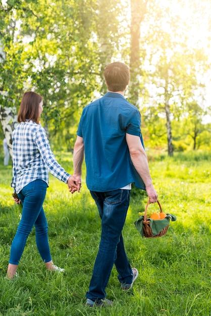Paar dat met picknickmand loopt op open plek Gratis Foto
