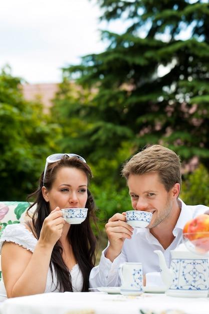 Paar dat ontbijt met koffie in tuin heeft Premium Foto