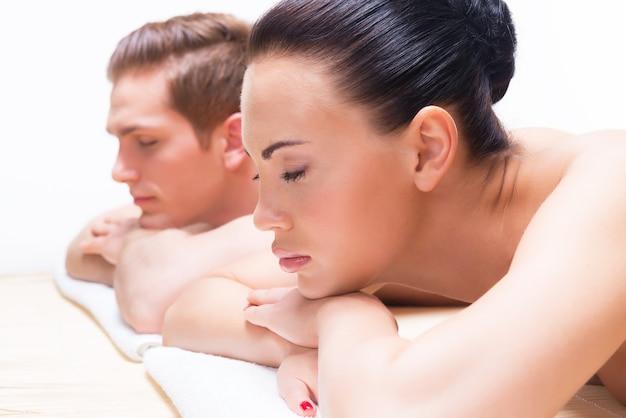 Paar dat op de massagebureaus op de kuuroordsalon ligt. schoonheidsbehandeling concept. Gratis Foto