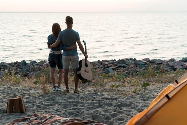 Paar dat op de zonsondergang let door het water Gratis Foto