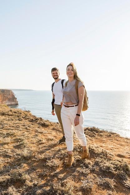 Paar dat op een kust naast de oceaan loopt Gratis Foto