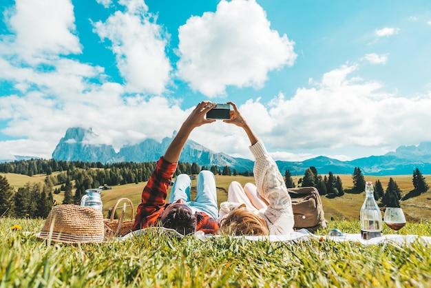 Paar dat op het gras ligt dat de alpen van tirol bezoekt. vriend en vriendin verliefd nemen van een foto van het landschap van de bergen met vintage camera - vintage filter - wanderlust-concept Premium Foto