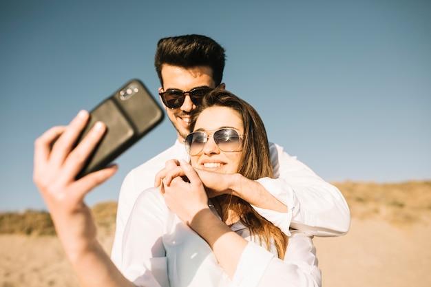 Paar dat op het strand loopt Gratis Foto