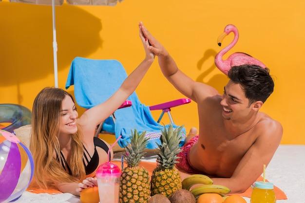Paar dat op strand met vruchten rust Gratis Foto