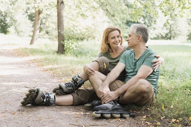 Paar dat rolschaatsen draagt die op het gras zitten Gratis Foto