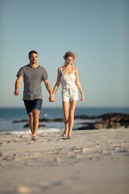 Paar dat samen hand in hand op het strand loopt Gratis Foto