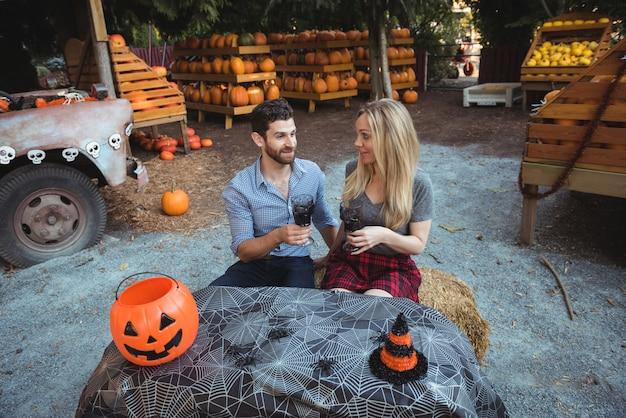 Paar dat terwijl het hebben van een glas wijn op elkaar inwerkt Gratis Foto