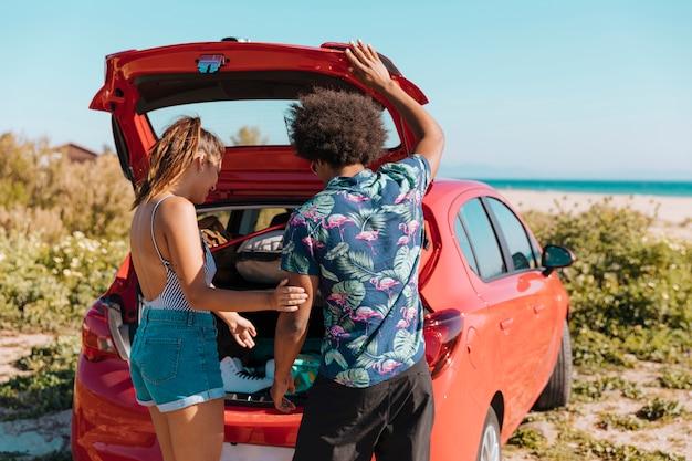 Paar dat zich dichtbij open boomstam van auto bevindt door kust Gratis Foto