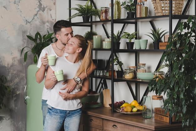 Paar dat zich in keuken bevindt die van elkaar houdt Gratis Foto