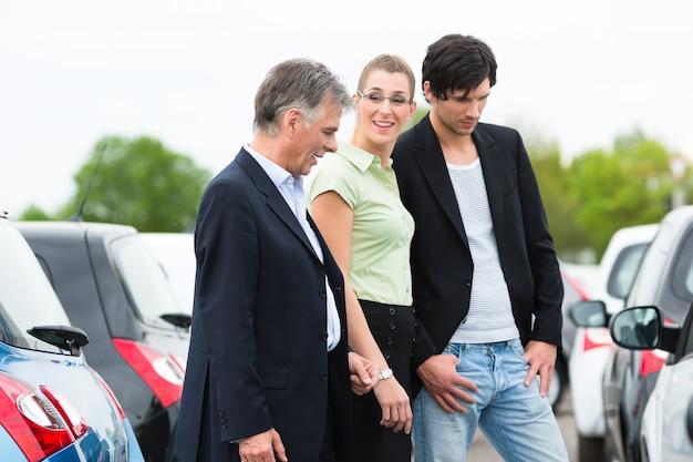 Paar die auto op werf van handelaar bekijken Premium Foto