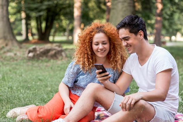 Paar die celtelefoon in het park controleren en pret hebben Gratis Foto