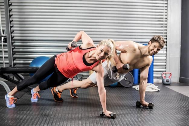 Paar die duw met domoren doen bij crossfitgymnastiek Premium Foto