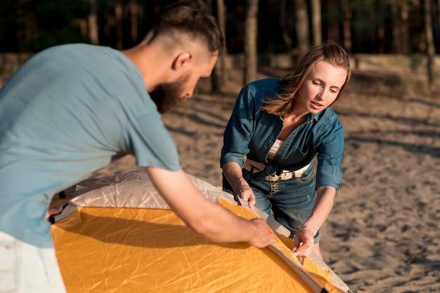 Paar die elkaar helpen de tent plaatsen Gratis Foto