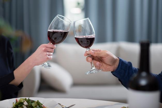 Paar die glazen wijn hebben bij de dagdiner van hun valentijnskaart Gratis Foto