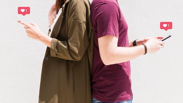 Paar die het rijtjes gebruiken van cellphone met de pictogrammen van liefdeberichten tegen muur bevinden zich Gratis Foto
