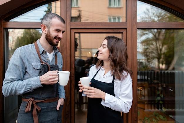 Paar die in schorten van koffie buiten winkel genieten Gratis Foto