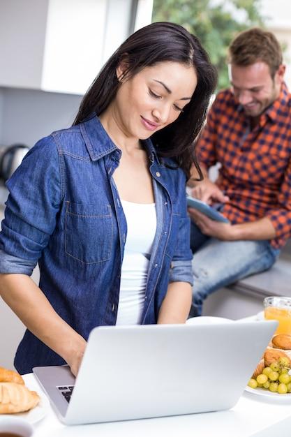 Paar die laptop en digitale tablet in de keuken gebruiken Premium Foto