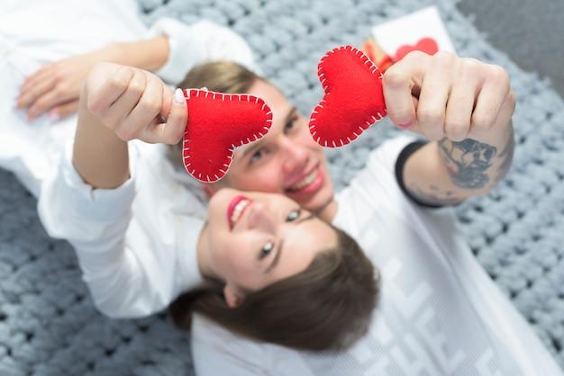 Paar die rode stuk speelgoed harten in handen houden Gratis Foto