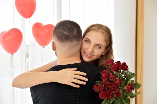 Paar die roze bloem in slaapkamergeluk geven in de dag selectieve nadruk van de valentijnskaart Premium Foto