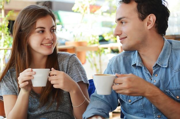 Paar die van een koffie genieten bij de koffiewinkel Premium Foto