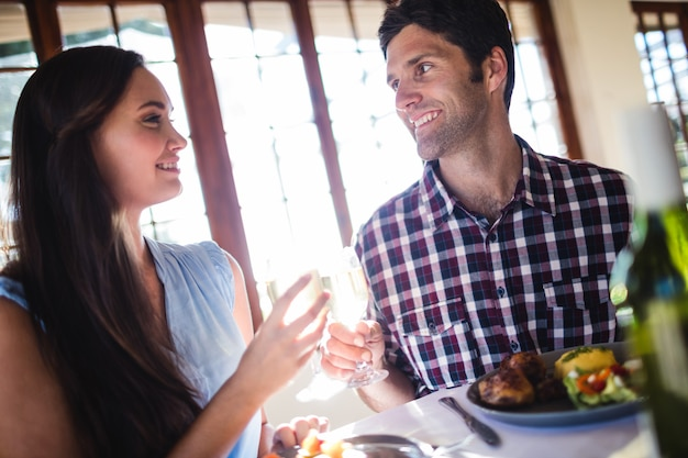 Paar die wit wijnglas in restaurant roosteren Premium Foto
