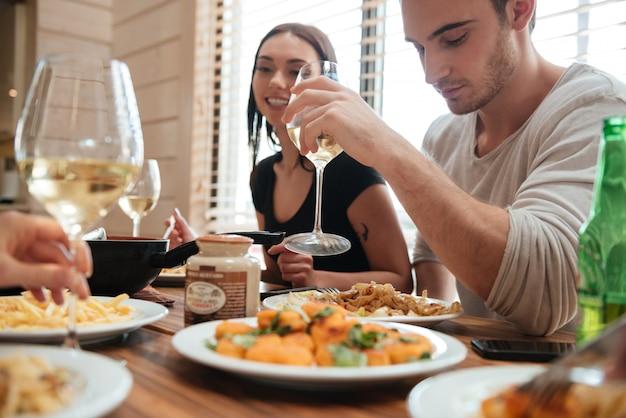 Paar eten en drinken van wijn met vrienden op de keuken Premium Foto