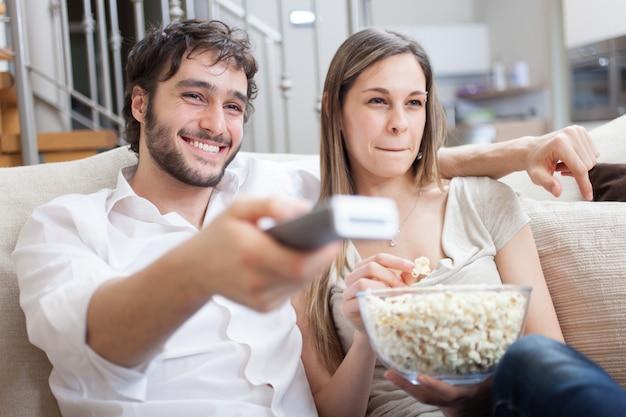 Paar eten popcorn tijdens het kijken naar een film Premium Foto