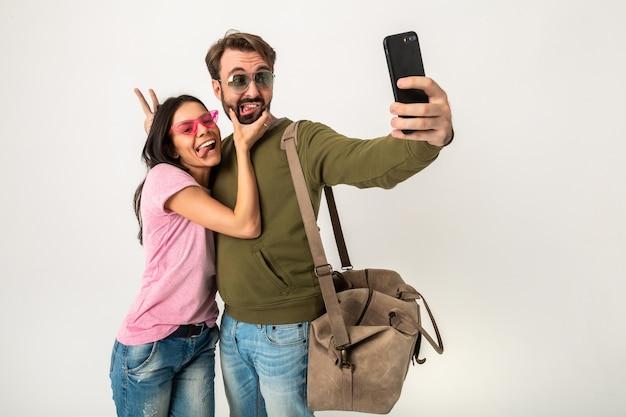 Paar geïsoleerde, vrij lachende vrouw in roze t-shirt en man in sweatshirt met reistas, spijkerbroek en zonnebril dragen, plezier hebben, samen reizen maken van grappige selfie foto op telefoon Gratis Foto